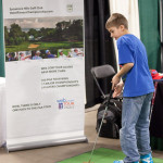 A young golfer practices his putting at the Northern Indiana Golf Show.